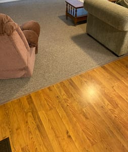 Flat wooden path from dining room to carpeted living room