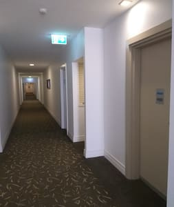 Night time view of well light, wide corridor entry to the apartment.  The apartment door is just a few steps from the lifts.