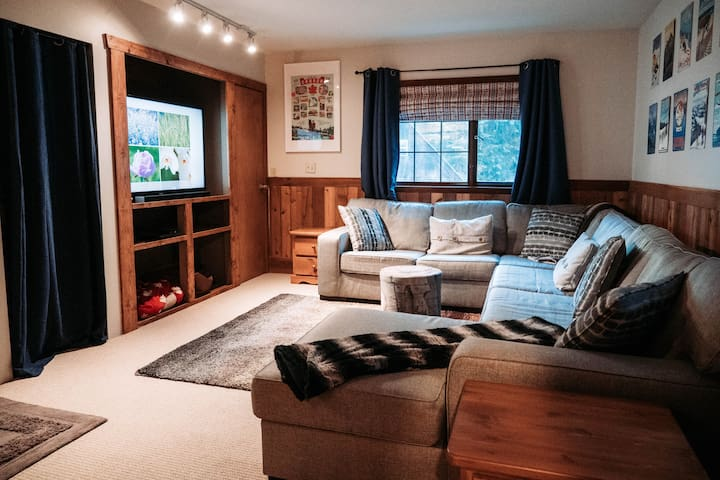 """Lower level entertainment room with 60"""" HD TV and enormous comfy couch and pull out queen bed."""