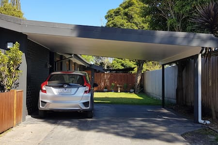 Carport with even surface and a path that runs along the side of the house to the Guesthouse entrance