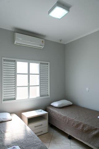 Quarto 01  Quarto com duas camas solteiro, ar condicionado, bancada lateral e aparador.