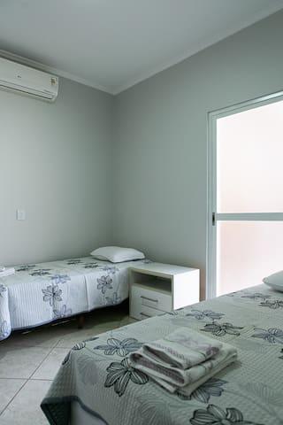 Quarto 02  Quarto com duas camas solteiro, ar condicionado, bancada lateral e aparador. Porta de correr saída para área da piscina.