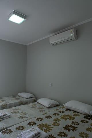 Suite 02  Quarto com 1 cama de casal e duas camas solteiro, ar condicionado, bancada lateral e aparador. Porta de correr saída para área da piscina.