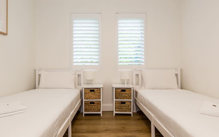 The second bedroom features two single beds, side table draws and a wardrobe.