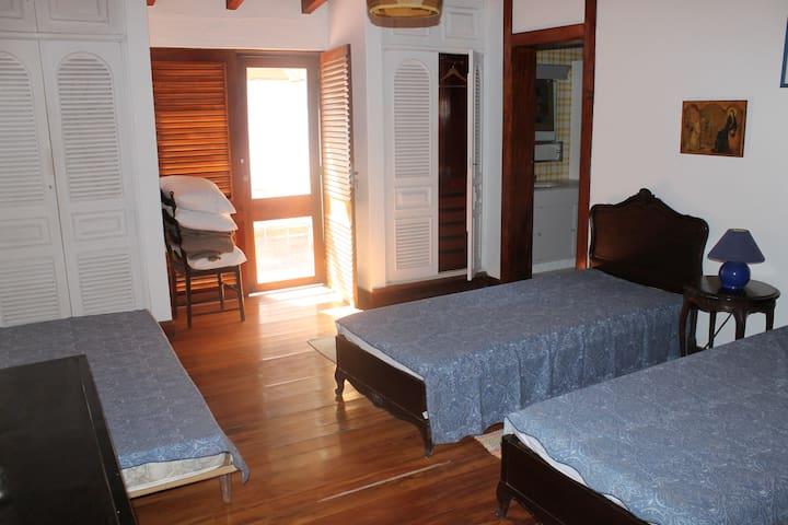 Quarto com três camas de solteiro e banheiro em suite