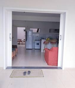 A portas principal tem 2metros de largura.  Para acessá-la tem um degrau de 5 centímetros entre a área aberta e o  hall de entrada da casa e um degrau de 5 centímetros entre a calçada e a referida área.