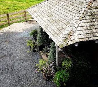the entrance to the barn is under a wooden porch with uneven set stone pavings, then a step up onto a concrete step then a wooden door surround into the ground floor