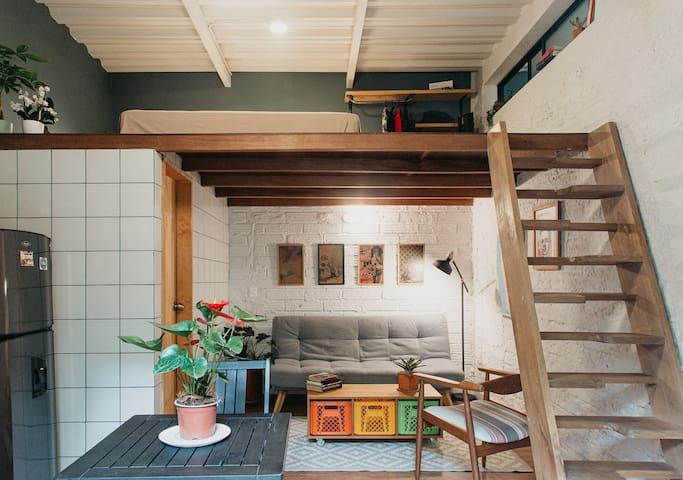 Cozy space with small dining room, kitchen, living room, private bathroom and stairs to the mezzanine / dormitory