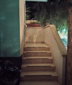entering the bamboo gate and climbing 6 stairs to the entrance door and then 15 stairs to the first floor apartment.