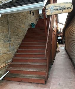 The walkway along the stairs, leads guests to the side door entrance to your South (left).  Free handicap street parking East of the walkway.