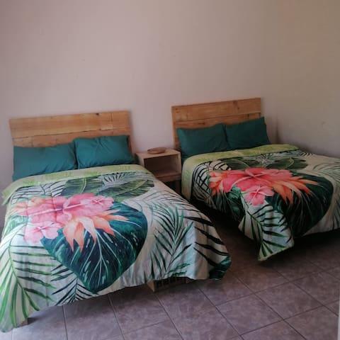 Recamara con dos camas tamaño matrimonial , en planta baja, con ropero y gran ventana.