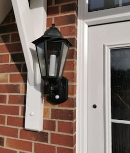Carriage light adjacent to the front door activated by motion-sensor, or by manual on/off