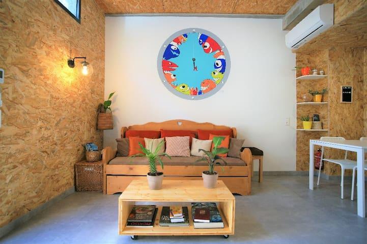 Coin salon, un coin salon, canapé convertible, table basse, espace cosy et informations, fresque murale peinte à la main