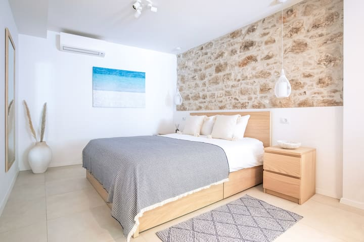 The bedroom area features a queen-size bed. The two hanging lights above each nightstand and a well-preserved original stone wall give this space a distinctive charm and coziness.