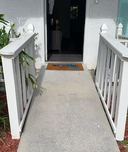 Gentle sloping ramp from flat parking area provides barrier-free entry.