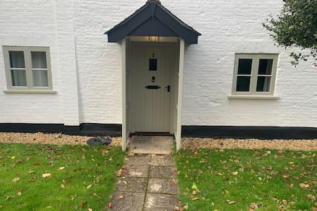 The front entrance has a lawn and concrete path leading to it (the path has a gradual downwards slope)
