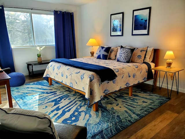 The largest of the three master suites has a big screen television, king bed, walk-in closet, two side chairs, an ottoman, coffee table, bed side tables, lamps, alarm clock, and room darkening curtains next to a private bath and walk-in closet.