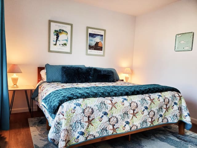 The master suite on the west side of the house has a king bed, large closet, side chair, ottoman, television, alarm clock, extra throws, and room darkening curtains as well as its own private bathroom.