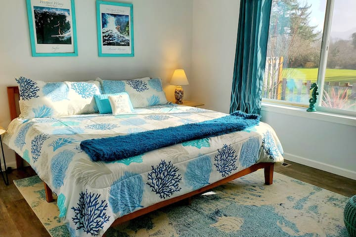 The master suite on the east side of the house has a view of the golf course. It boasts a king bed, a comfy throw, a lounge chair and ottoman, large closet, room darkening curtains, television, alarm clock and double side tables with lamps.