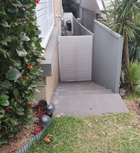 When facing the house, your entry is to the right hand side.  Enter down a few steps and through the white gate.