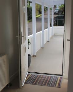 Cottage front door entrance with smooth wide tiled entrance with low threshold on door space.