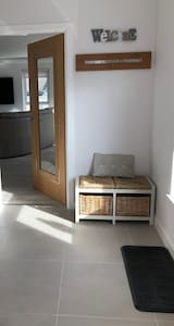 Wide entrance vestibule that is tiled with low threshold fitted to door that leads into open plan living space.