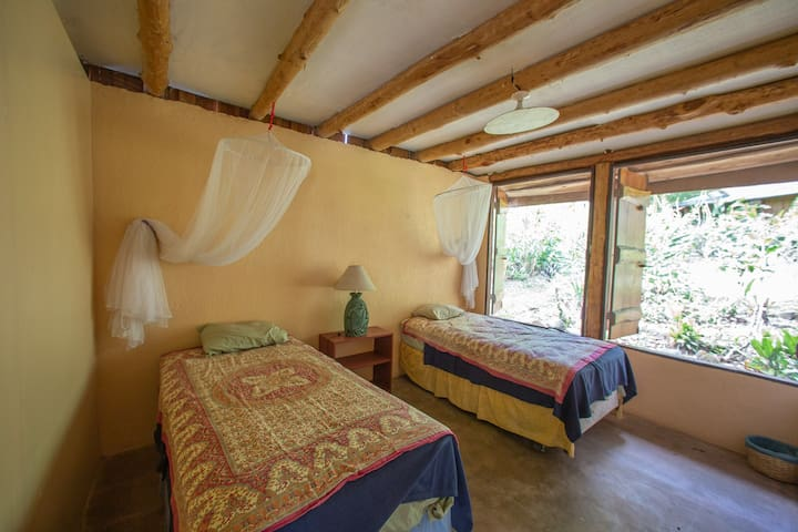 Bedroom number 2 with two single beds. The windows are screened and close with cedar shutters.