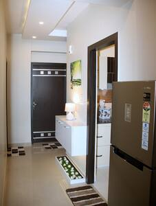 The corridor is  nearly 36 inches wide with slight constrictions near the refrigerator and wall slimline side board for night lamp; as shown in image.