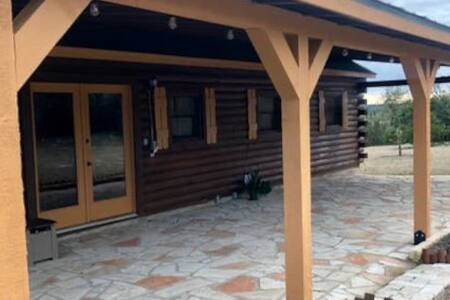 """The front entrance is located on the same level as the parking.  The entrance is a rock patio with an approximate 4"""" step up on the door threshold."""