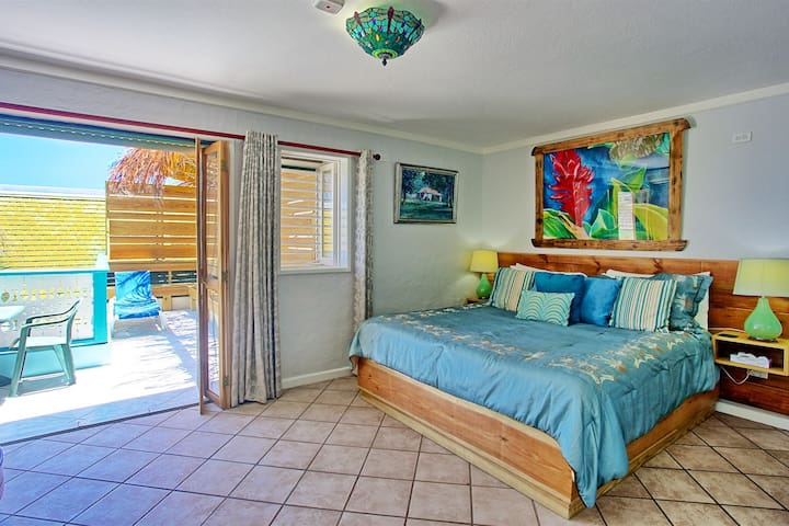 Bedroom 7. King size bed, TV, En Suite Bath with Shower, Balcony overlooking pool and Caribbean sea, spacious seating area.