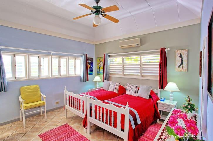 Bedroom 2. Two twin beds,  twin-to-king converter, En suite Bath with Shower, TV. Door connects with  bedroom 3.