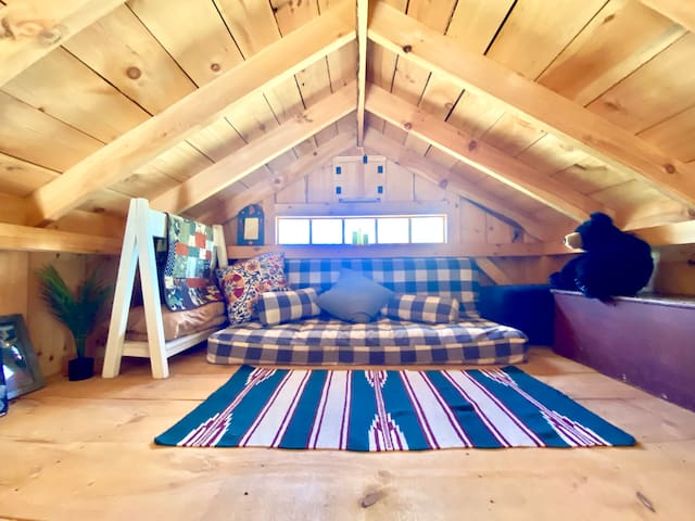 A cool view of the loft. The futon mattress can be pulled down for a full size bed.  Extra blankets, pillows, towels, books and games can be found up here.