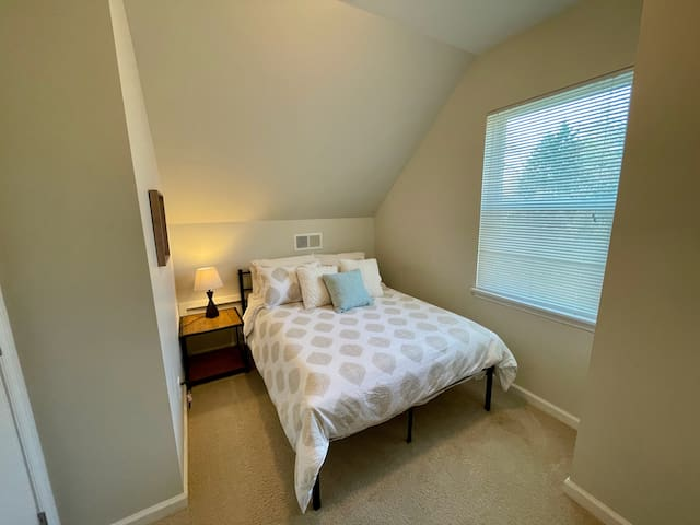 Cozy upstairs bedroom with full-sized bed.