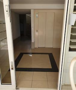Hall d'entrée avec au premier plan l'ascenseur, à gauche en arrière-plan l'escalier.