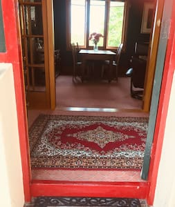 Front door and entrance into main hallway. There is a step over the front door into main hallway