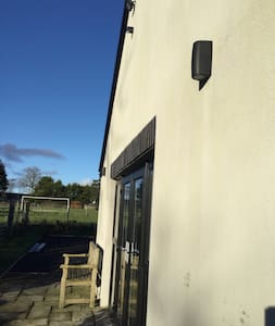 Two wall mounted lights at either side of doorway and security light situated at top middle of building.