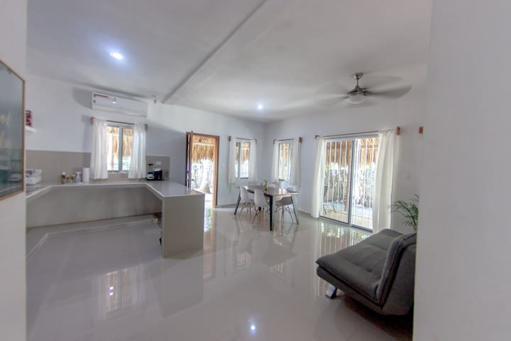 Open kitchen, dining and lounge area with sofa bed.