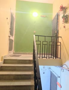 This the entrance to the flat  It is well lit The stairs have an iron railing and soft steps