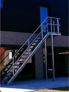 De ingang naar het gastenverblijf. De weg en trap wordt verlicht met spots die aangaan door sensor.