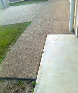 Level pathway from the driveway towards the front patio. Distance between edge of path and downpipe is 110 cm.