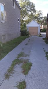 Driveway off of Cassells Street. Drive in and veer to the right to enter the large parking area at the back of the house.