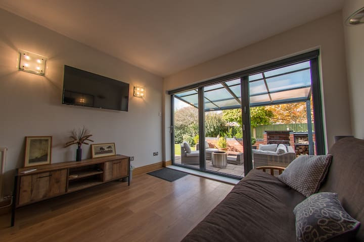 Garden bedroom showing covered patio with fire pit and barbecue.  It is normally set up as bedroom with double bed and room for single  There are drawers and hanging space.  TV with Netflix and blinds (not black out) with Remote control.