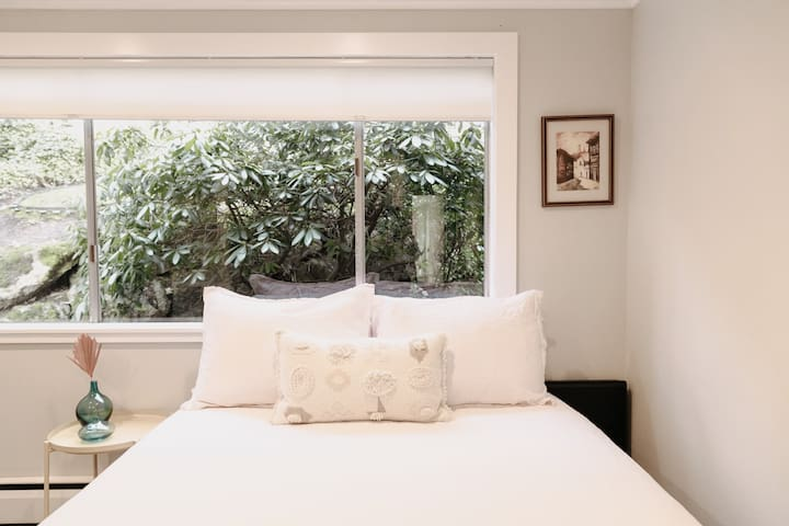Light and bright 2nd bedroom with comfortable queen bed, window with view of backyard greenery, home office, and full sized closet.