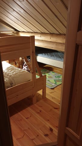 """Bunk bed with 120 cm wide lower bunk at the loft. Extra 90 cm bed in """"play cave"""" for the kids."""