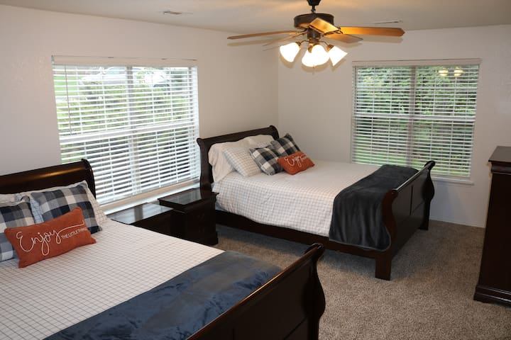 """Downstairs we have a master suite we like to call the """"double queen room"""" with 2 queen beds, nightstands and a chest of drawers.  This suite has a large double vanity bathroom and walk in closet."""