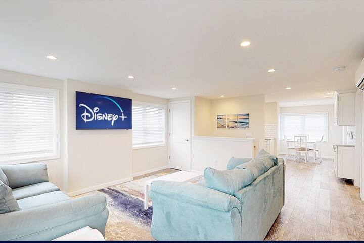 Light and bright living room area. Features plenty of seating and smart TV with FREE Disney+