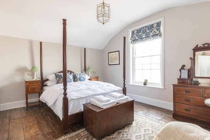 Sarah's master bedroom comes complete with a bespoke four-poster mahogany bed, The White Company bedding and towels, Pooky lampshades, and a sunset view out over rooftops looking towards the North Norfolk coast.