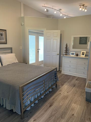 Bedroom with queen size bed, dresser, and walk in closet with hangers and plenty of space for luggage storage.