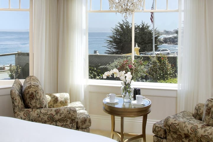 Seven Gables Inn boutique. hotel. China Point room is on the elevated 1st floor of the Beach House. Bay window looks down the coast and overlooks the garden area. King pillow top bed, comfortable chairs  and armoire.