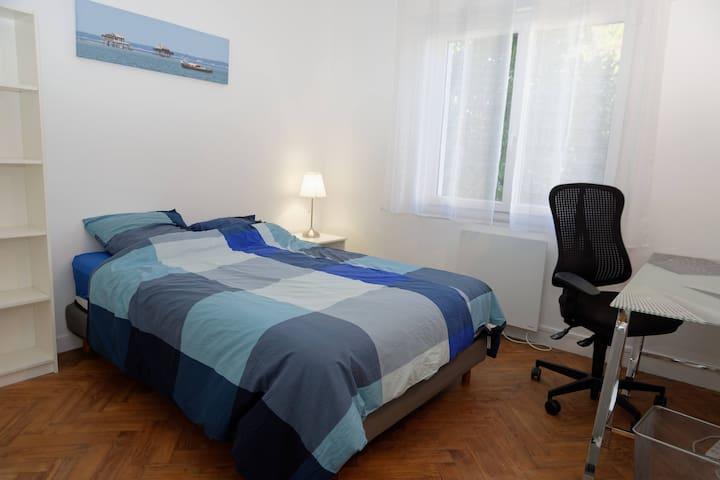 Chambre avec un grand lit en 150 x 200 avec un matelas neuf Armoire, placard, bureau. Vue sur le jardin côté Ouest (très calme)